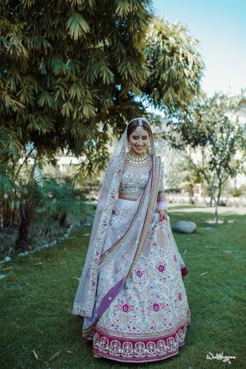 Photo of bride in a white and red floral work lehenga with double dupatta