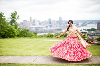 Bride twirling in red and gold gota patti lehenga