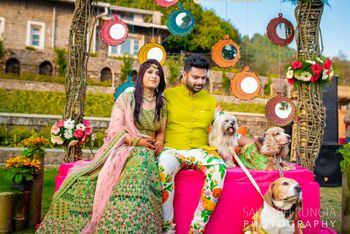 Photo of A bride and groom pose with their dogs at their mehendi