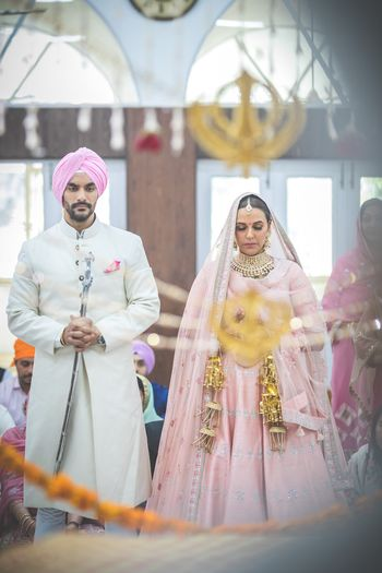 Celebrity couple Angad Bedi and Neha Dhupia in color coordinated outfits at their anand karaj