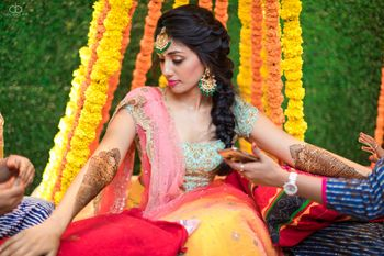 Photo of Bride getting mehendi put with genda phool backdrop