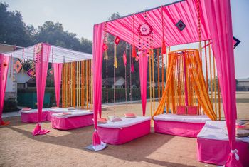 Photo of Mehendi decor idea with seating with pink and orange theme