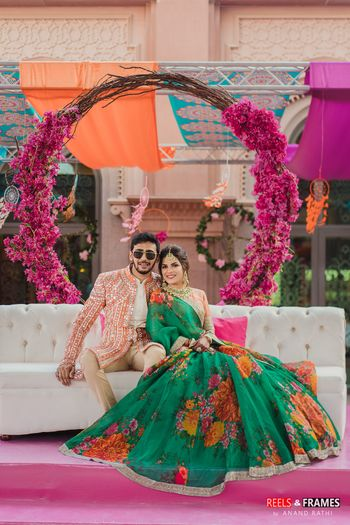 A bride and groom in colorful and coordinated outfits for their mehndi