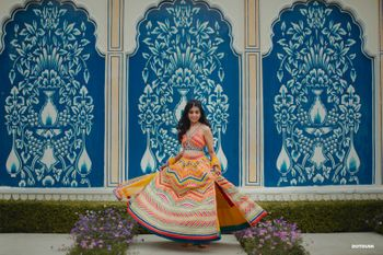 A twirling bride in a mutlicoloured lehenga with a side slit