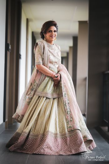 Photo of stylish mother of the bride in a pastel lehenga
