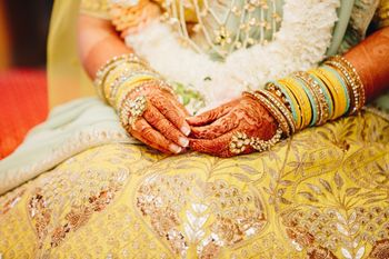 Bridal hands on yellow gota patti lehenga