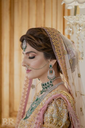 bride with glossy bridal makeup and emerald jewellery