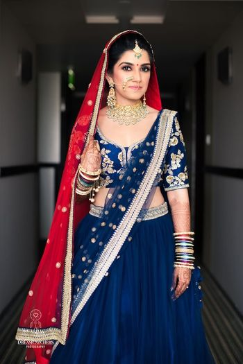 Photo of Offbeat bridal lehenga with blue dupatta and red on head