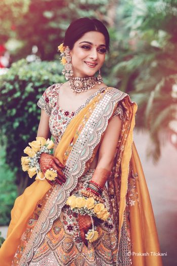 Bridal portrait in a yellow mehendi lehenga on her mehendi