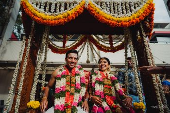 Couple portrait on a jhoola with genda phool decor