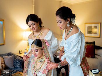 Photo of Bridesmaids helping bride get ready