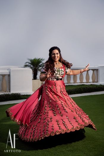 Photo of Twirling bride in bright coral lehenga