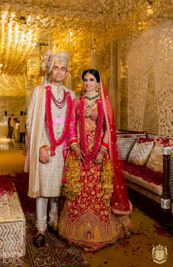 contrasting bride and groom outfits with both wearing red jaimalas