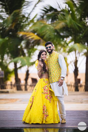 A bride in groom in coordinated yellow mehendi outfits