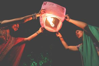Photo of Releasing  paper lanterns into night sky whhile the couple sits on the feras
