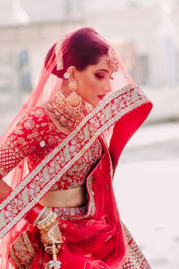 beautiful bridal portrait idea with the red dupatta as veil