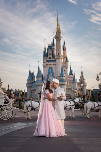 Bride and groom post in front of castle at Disney World, Orlando