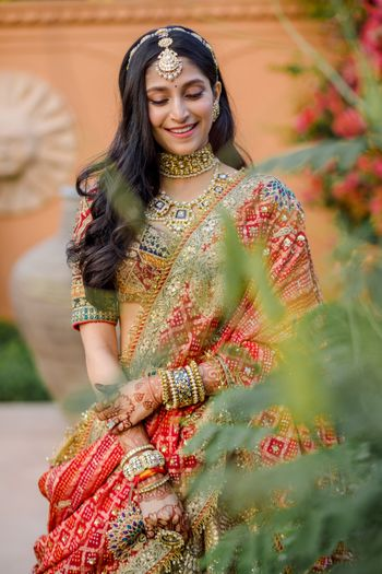 Photo of Bride wearing a multi-coloured lehenga.