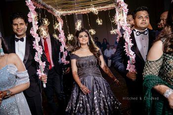 A bride dressed in grey gown entering under a unique phoolon ki chadar