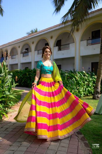 A bride in a multi-colored lehenga for her morning mehndi ceremony