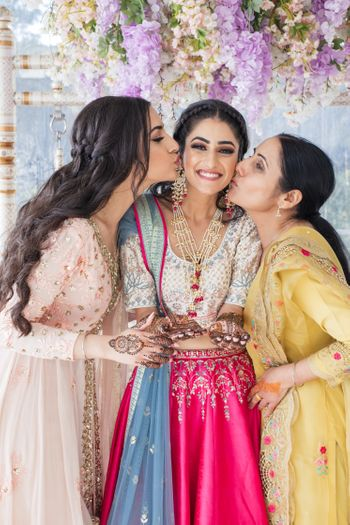 Photo of Bride posing with her mother and sister on her Mehndi ceremony.