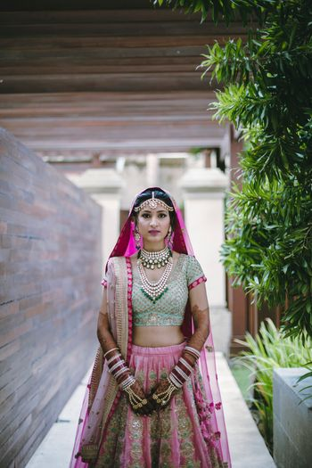 Photo of Bride posing in green and pink bridal lehenga with double dupatta