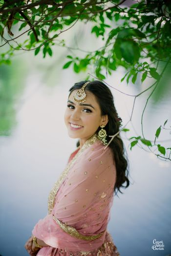 A bride in a light pink outfit for her mehndi