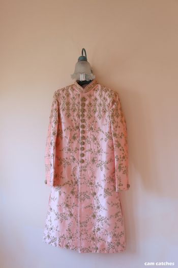 Light pink sherwani on a hanger with embroidery