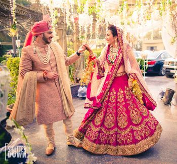 Bride and groom in fuschia pink coordinated outfits