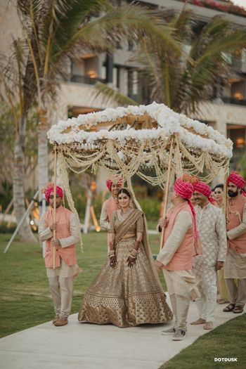 A bride entering under a gorgeous phoolon ki chaadar with tassels and white flowers