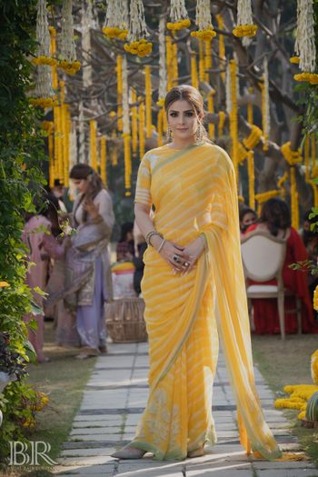 sister of the bride in yellow striped saree on mehendi