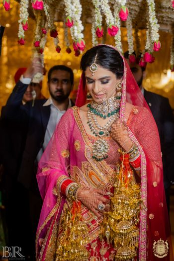 bridal entry in red lehenga and unique jewellery