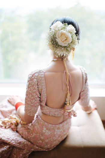 Bride wearing a floral bouquet bun with a pink lehenga.