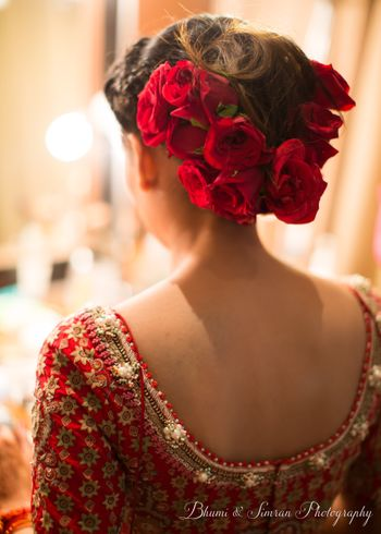 A bride getting her hair done with roses on wedding day