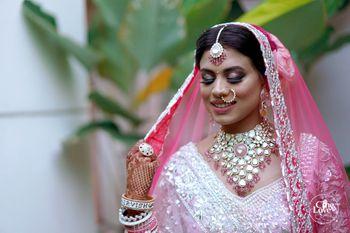 Bride wearing pink lehenga and jewellery