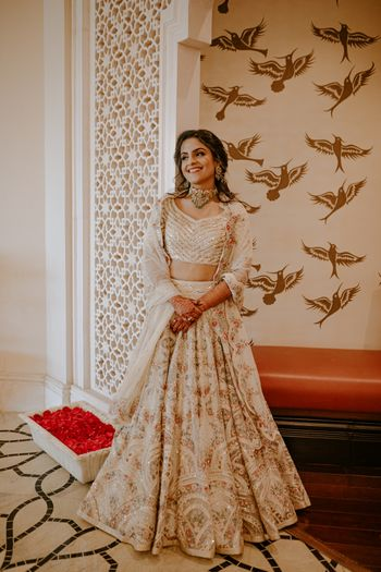 Bride wearing a detailed ivory lehenga on her Mehendi