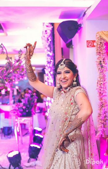 Dancing bride in beige lehenga