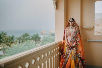 Photo of unique bridal lehenga in orange with matching chuda