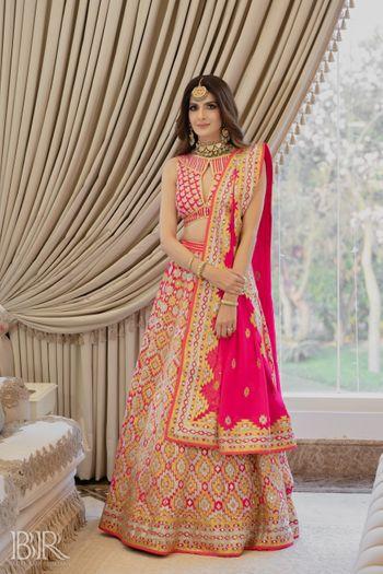 Photo of hot pink abu jani lehenga with unique blouse