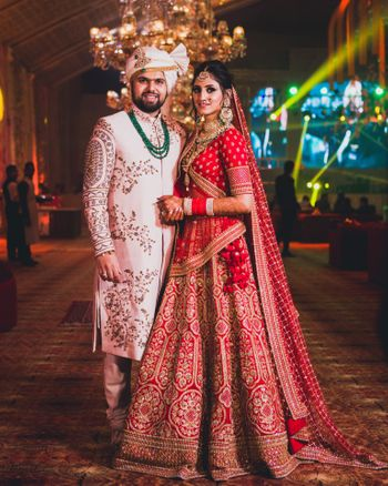 Photo of Contrasting bride and groom outfits in red and white