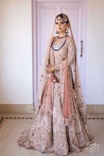A beautiful bride in peach bridal heavy sharara and exquisite jewellery with dark blue beads.
