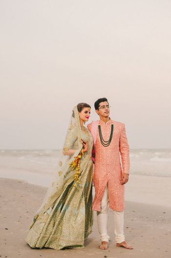 Photo of Contrasting bride and groom outfits on the beach