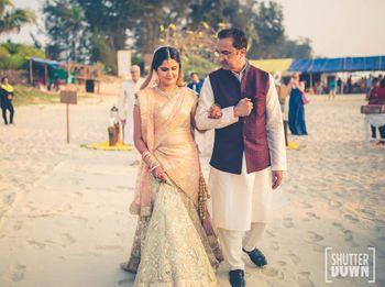 Bride in pastel lehenga entering beach wedding