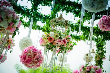 Photo of Pink and green birdcages with pearls and floral balls