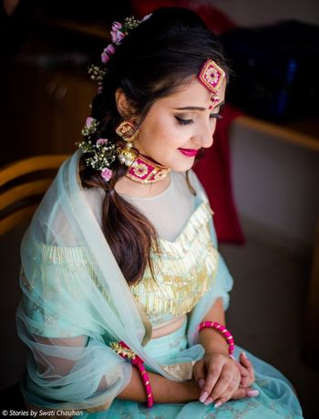 Bride with unique mehendi jewellery and flowers in short braid
