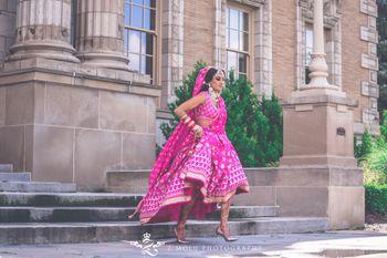 Bride walking in bright pink lehenga
