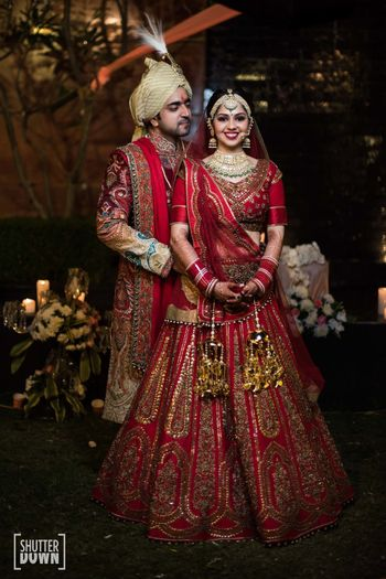 Photo of Matching bride and groom in red outfits