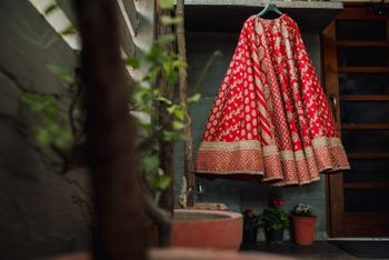 Photo of Sabyasachi bridal lehenga on hanger red and gold