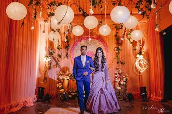 Photo of A bride in a gown and a groom in a blue suit enter together for their sangeet/cocktail function.