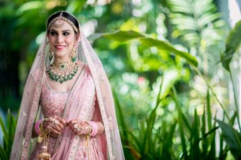 Bridal portrait with the bride in a pink Anita Dongre lehenga